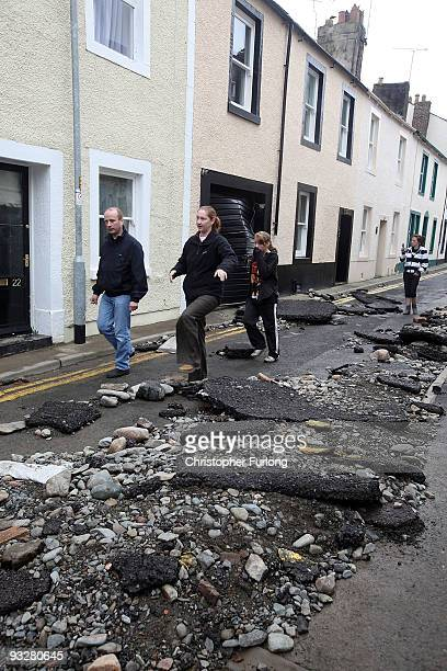 People walk down a damaged road as flood water recedes and the clean up begins on November 21, 2009 in Cockermouth, United Kingdom. A major rescue...