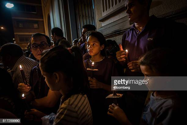 People walk down a dark street holding candles as they pass closed shops and offices during a Holy Week procession in eastern Caracas Venezuela on...