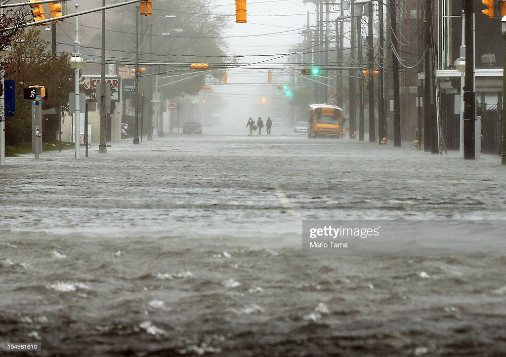 CITY, NJ - OCTOBER 29 People walk down a flooded street as Hurricane Sandy moves up the coast on October 29, 2012 in Atlantic City, New Jersey. Governor Chris Christie's emergency declaration is shutting down the city's casinos and 30,000 residents were ordered to evacuate.