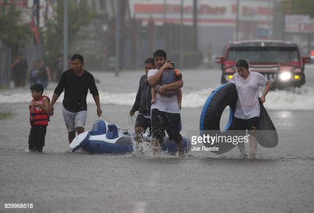 People walk down a flooded street as they evacuate their homes after the area was inundated with flooding from Hurricane Harvey on August 27, 2017 in...