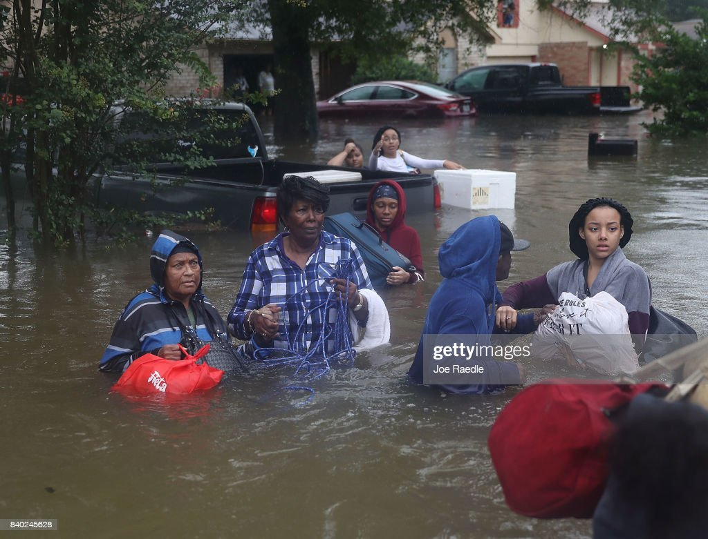 People walk down a flooded street as they evacuate their homes after the area was inundated with flooding from Hurricane Harvey on August 28, 2017 in Houston, Texas. Harvey, which made landfall north of Corpus Christi late Friday evening, is expected to dump upwards to 40 inches of rain in Texas over the next couple of days.