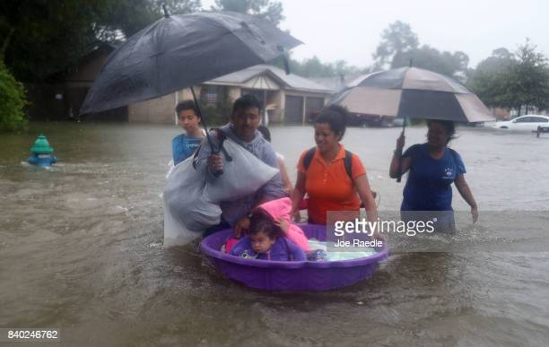 People walk down a flooded street as they evacuate their homes after the area was inundated with flooding from Hurricane Harvey on August 28, 2017 in...