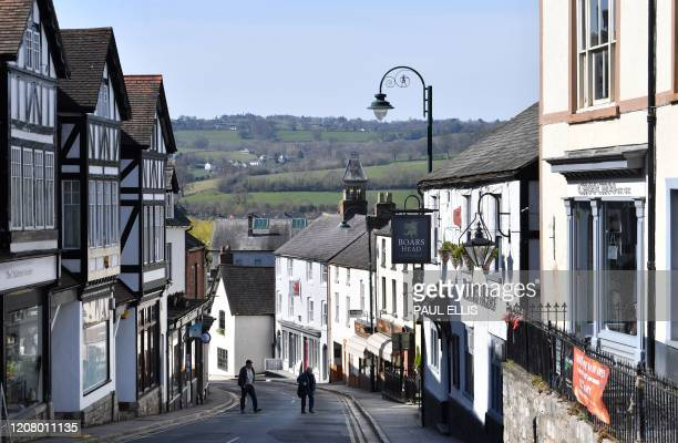 People walk down a quiet high street in Ruthin, north Wales on March 23, 2020. - Prime Minister Boris Johnson warned on Sunday he may impose tougher...
