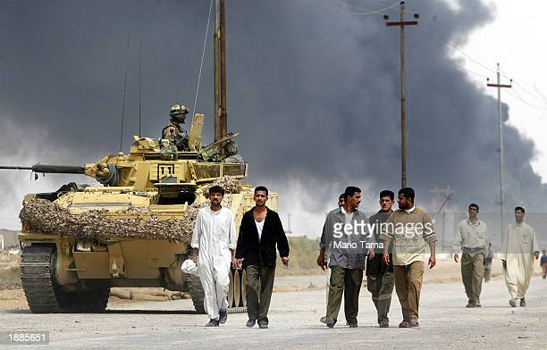 People walk down a road out of Basra as fighting continues in the city March 30, 2003 in Basra, Iraq. Coalition forces launched more air raids on the...
