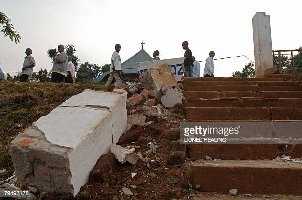 People walk down a road past rubble 03 February 2008 in Bukavu An eathquake measuring 60 on the richter scale shook this region of eastern Congo as...