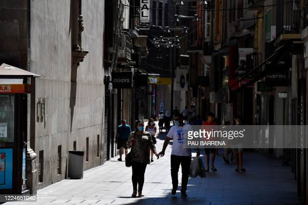 People walk down a shopping street in Lleida on July 4, 2020. - Spain's northeastern Catalonia region locked down an area with around 200,000...