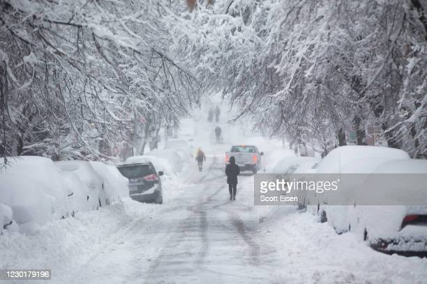 People walk down a snow-covered Chestnut Street on December 17, 2020 in Boston, Massachusetts. More than a foot of snow is expected in the Greater...