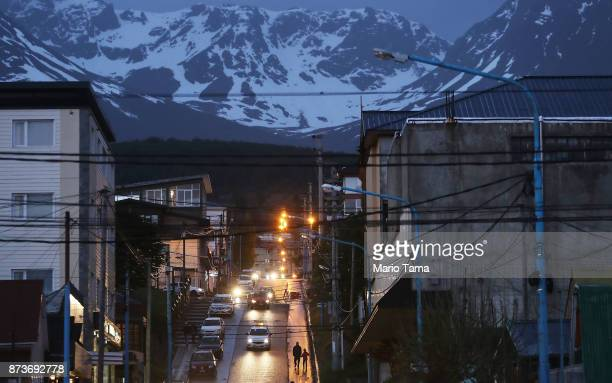People walk down a street at dusk on November 7 2017 near Ushuaia Argentina Ushuaia is situated along the southern edge of Tierra del Fuego in the...