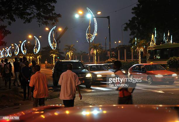 People walk down a street decorated with Christmas lights in the Plateau business district of Abidjan on December 23 2013 AFP PHOTO/ SIA KAMBOU