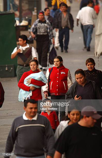 People walk down a street in a predominantly Latin American immigrant section of the community of Westlake on January 22 2003 in Los Angeles...