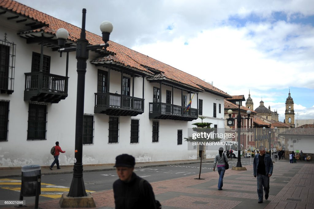 People walk down a street in the historic neighborhood of La Candelaria in Bogota on September 17, 2009