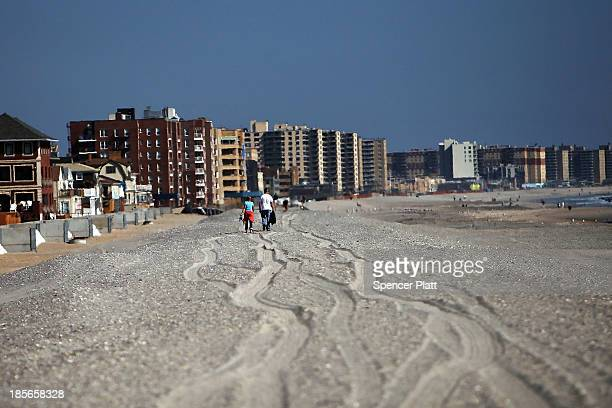 People walk down a stretch of beach that was heavily damaged during Hurricane Sandy on October 19 2013 in the in Rockaway neighborhood of the Queens...
