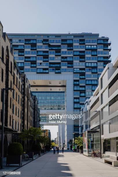 people walk down long pedestrian walkway under the kranhaus modern architecture - stadtviertel stock-fotos und bilder