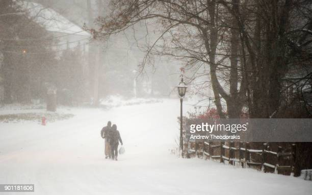 People walk down main st as a blizzard hits the Northeastern part of the United States January 4 2018 in Stony Brook New York