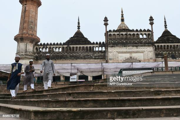 People walk down stairs next to the mosque at the Bara Imambara a colossal imambara complex in Lucknow northern India on August 25 2017 / AFP PHOTO /...