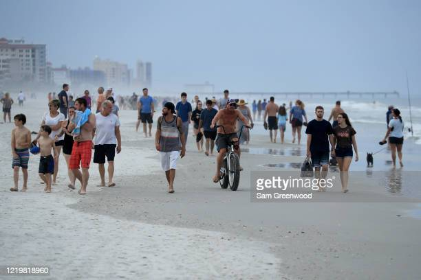 People walk down the beach on April 19, 2020 in Jacksonville Beach, Florida. Jacksonville Mayor Lenny Curry announced Thursday that Duval County's...