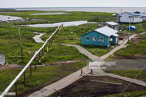 People walk down the elevated, raised wooden sidewalks - created so people don't sink into the melting permafrost - on July 5, 2015 in Newtok,...