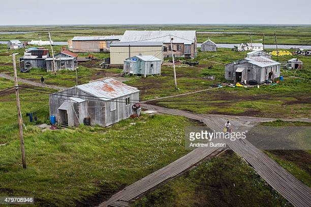 People walk down the elevated raised wooden sidewalks created so people don't sink into the melting permafrost on July 5 2015 in Newtok Alaska Newtok...