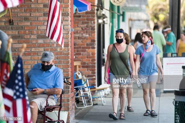 People walk down the sidewalk on July 17, 2020 in St. Simons Island, Georgia. Georgia Gov. Brian Kemp made an order earlier in the week that forbade...