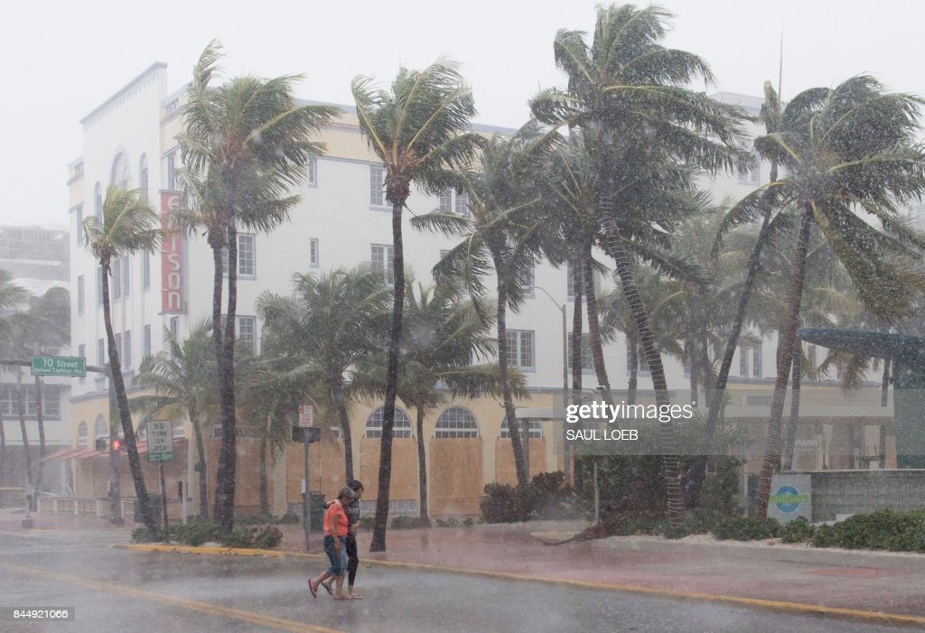 TOPSHOT - People walk down the street as winds and rain begin to hit as outer bands of Hurricane Irma arrive in Miami Beach, Florida, September 9, 2017. Hurricane Irma weakened slightly to a Category 4 storm early Saturday, according to the US National Hurricane Center, after making landfall hours earlier in Cuba with maximum-strength Category 5 winds. /