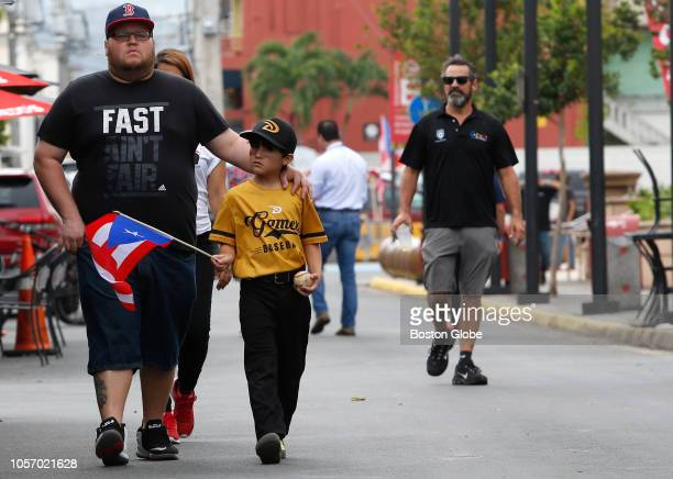 People walk down the streets of Caguas towards a rally for Red Sox manager Alex Cora's return to his hometown with the World Series trophy Red Sox...