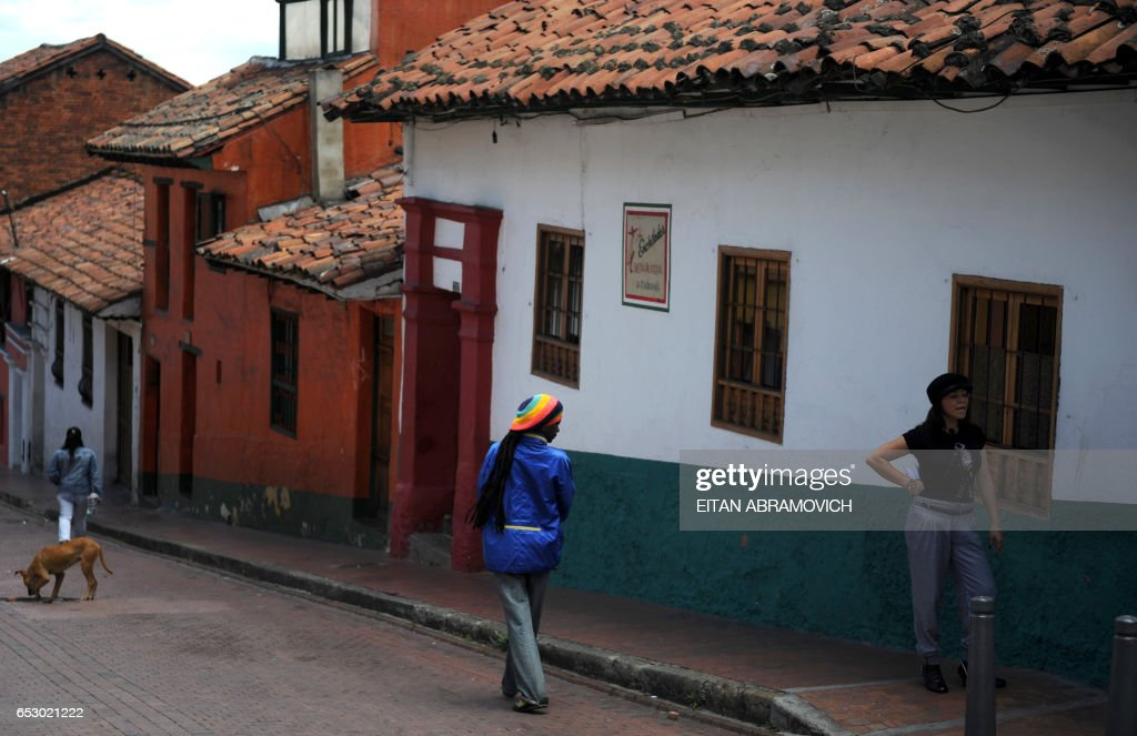 People walk down the streets of the historic neighborhood of La Candelaria in Bogota on September 17, 2009