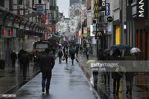 People walk down the the Rue Neuve pedestrian shopping street in Brussels on November 21 2015 All metro train stations in Brussels will be closed on...