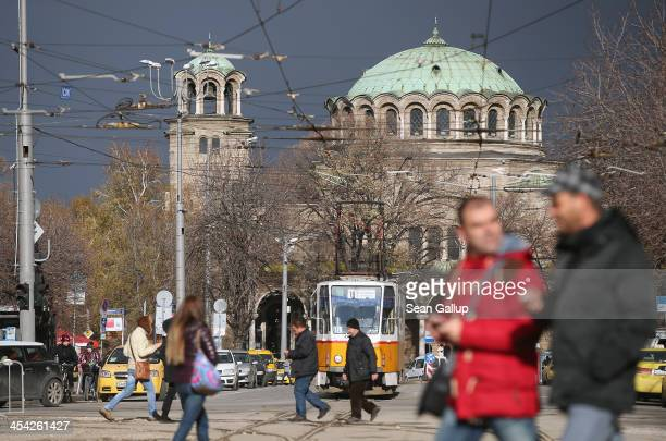 People walk down the Vitosha Boulevard shopping street as the St Nedelya Eastern Orthodox church stands behind on December 7 2013 in Sofia Bulgaria...
