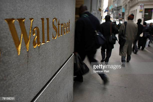 People walk down Wall Street January 22 2008 in New York City Following a sharp fall in international markets Monday the Federal Reserve lowered its...