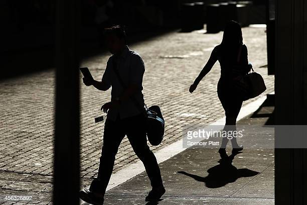 People walk down Wall Street near the New York Stock Exchange on September 29 2014 in New York City In morning trading the Dow opened down more than...