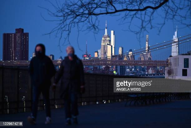 People walk during a cold evening on the Brooklyn Promenade on November 18, 2020 in New York City. - US states and cities are imposing a raft of new...