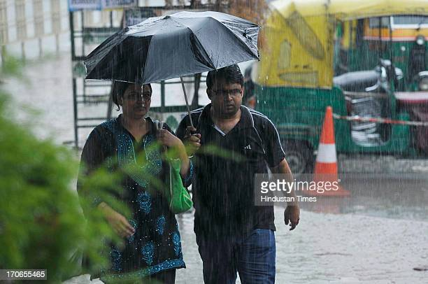 People walk during a heavy rainfall on June 16, 2013 in Noida, India. The national capital has been witnessing pre-monsoon showers, recording 6.1 mm...