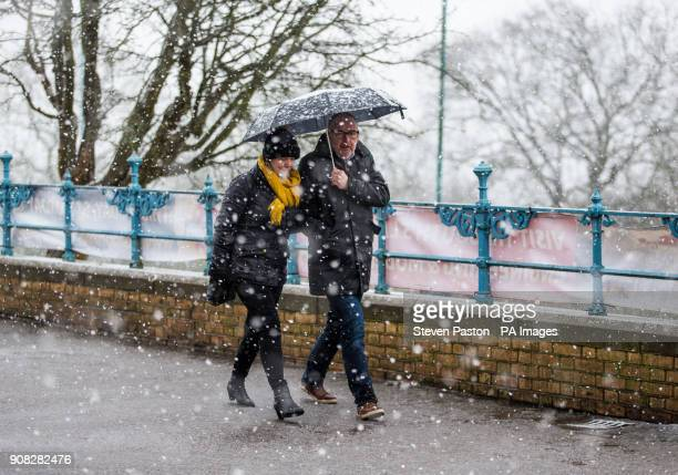 People walk during a snowfall at Alexandra Palace London as people across the country are braced for more snow after the UK froze on the coldest...