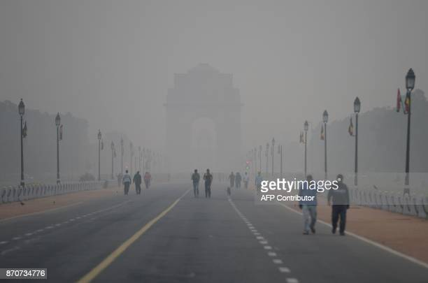 TOPSHOT People walk early in the morning as smog covers India Gate war memorial in New Delhi on November 6 2017 Delhi one of the world's most...