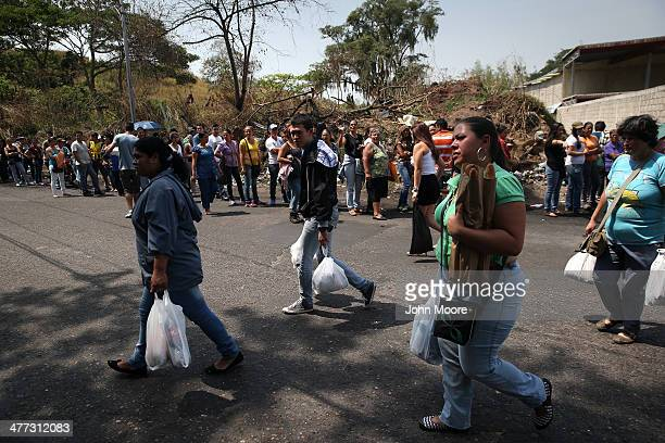 People walk home after waiting 4 hours to buy basic foodstuffs on March 8 2014 in San Cristobal the capital of Tachira state Venezuela Shortage of...