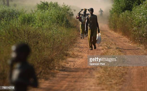 People walk home from work in the fields December 17, 2007 in Kaga Bandoro in the northern Central African Republic. Central African Republic is one...