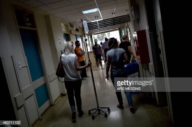 People walk in a corridor of an Athens hospital on July 8 2015 With expectations of a Greek exit from the eurozone gathering pace health officials...