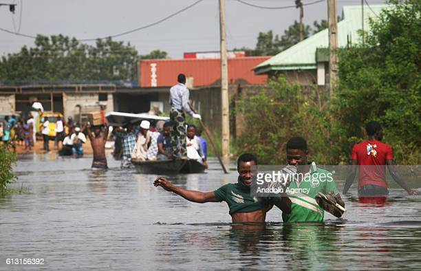 People walk in a flooded area after the Ogun region flooded following a day long torrential rain caused Ogun river to overflow in Lagos, Nigeria on...