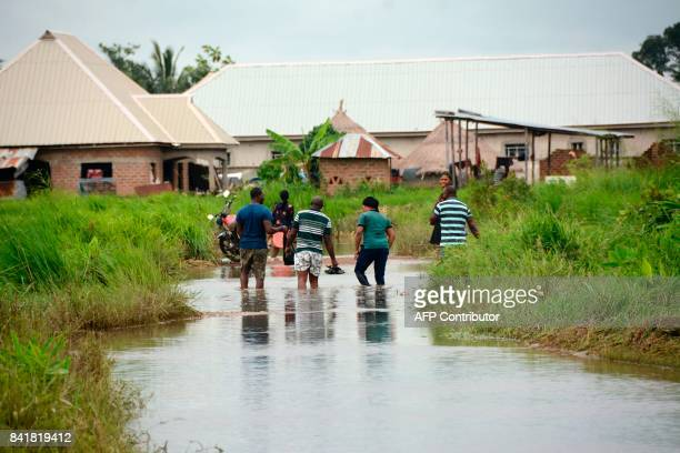 People walk in a flooded street as they evacuate the flooded area following heavy rains in Makurdi Benue State Nigeria on September 1 2017 At least...