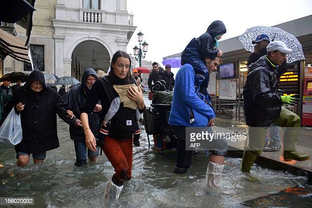 People walk in a flooded street during a 'acqua alta' on November 11 2012 in Venice Rain and wind hit the north of Italy on Sunday and the folooding...