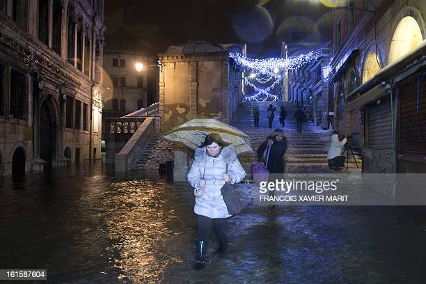 People walk in a flooded street during an acquaalta late on February 11 2013 in Venice The acqua alta a convergence of high tides and a strong...