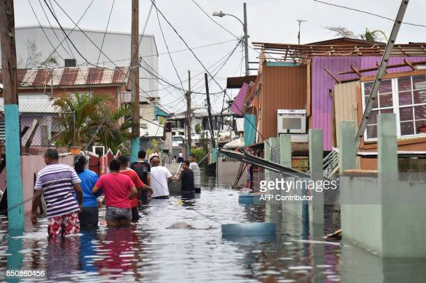People walk in a flooded street next to damaged houses in Catano town in Juana Matos Puerto Rico on September 21 2017 Puerto Rico braced for...