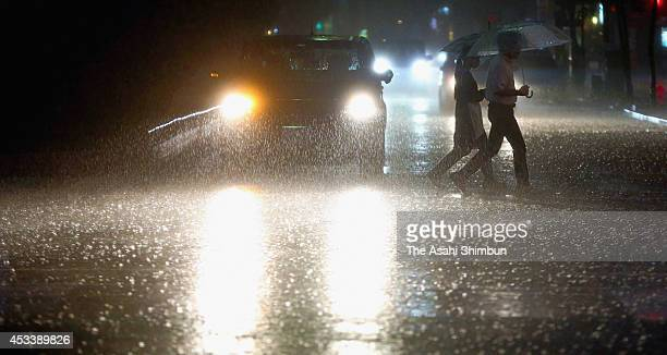 People walk in a heavy rain triggered by Typhoon Halong on August 9 2014 in Kochi Japan Typhoon Halong approaches to Shikoku Island local governments...