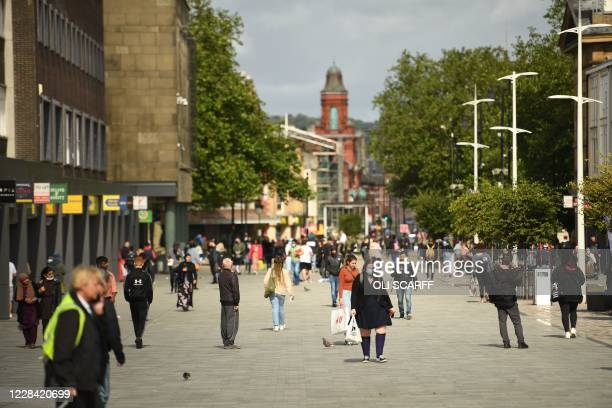 People walk in a high street in the centre of Bolton, northern England on September 9 as local lockdown restrictions are put in place due to a spike...