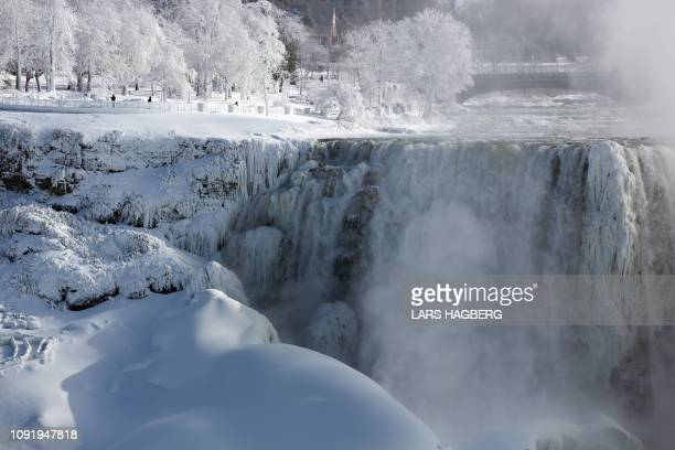 People walk in a park on the US side of Niagara Falls as seen from Niagara Falls Ontario Canada on January 31 2019 A brutal cold wave moved eastward...