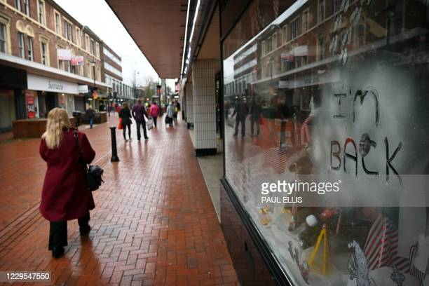 People walk in a shopping high street with 'I'm Back' written in a shop window in Wrexham, North Wales on November 9, 2020 as Wales emerges from a...