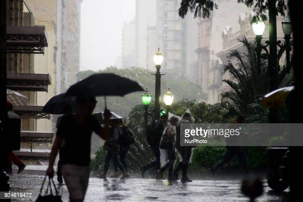 People walk in a shopping street in downtown Sao Paulo on rainy day afternoom Brazil February 26 2018
