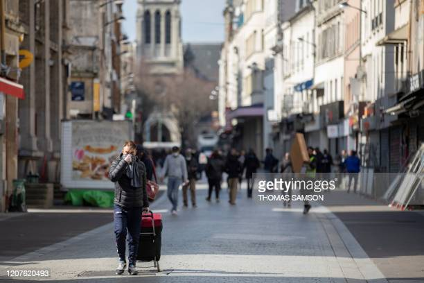 People walk in a shopping street of Saint-Denis, near Paris on March 18 after a strict lockdown came into effect in France to stop the spread of the...