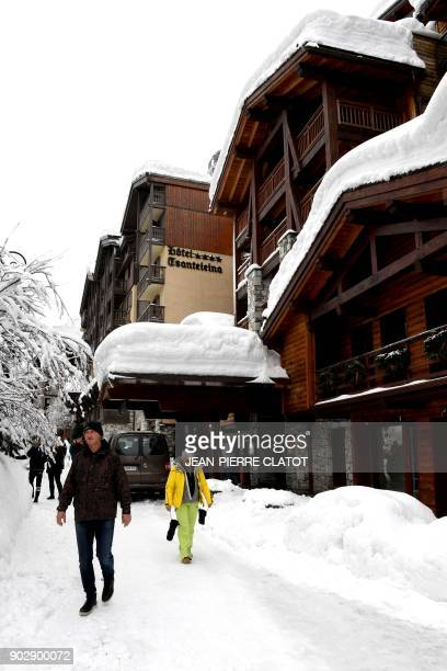People walk in a snowy street on January 9 2018 in Val d'Isere village in the French Alps following the reopening of the road after the snow has...