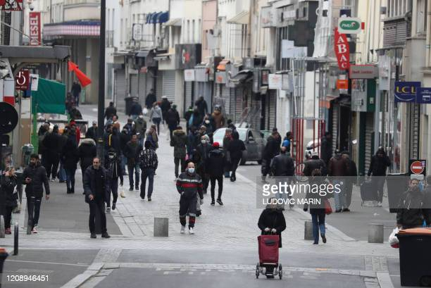 People walk in a street as they go for shopping on April 2, 2020 in Saint-Denis, near Paris, on the seventeen day of a lockdown aimed at curbing the...